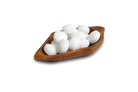 White naphthalene balls in a wooden bowl isolated on a white background.