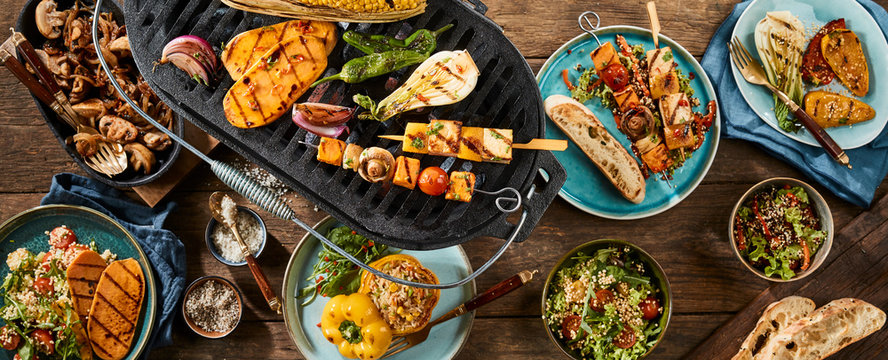 Vegetarian barbecue grilled dishes on timber table