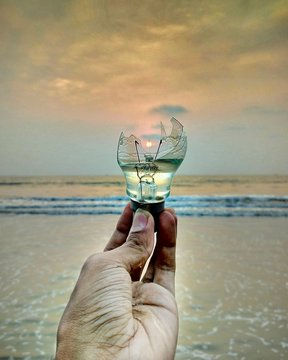 Cropped Hand Of Man Holding Broken Light Bulb At Beach
