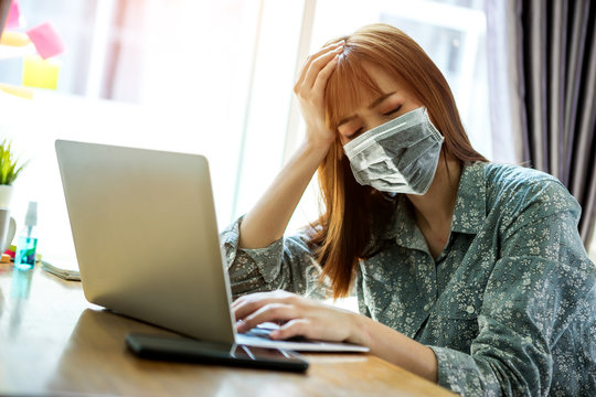 Young asian woman wearing mask protect covid-19 feeling strain fatigue and have a fever during working with laptop in her home. work from home concept