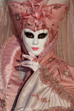 Venice Italy, February 08 2020. Close up of woman in decorated mask and ornate pink costume posing for the camera at St Mark's Square during Venice Carnival (Carnivale di Venezia