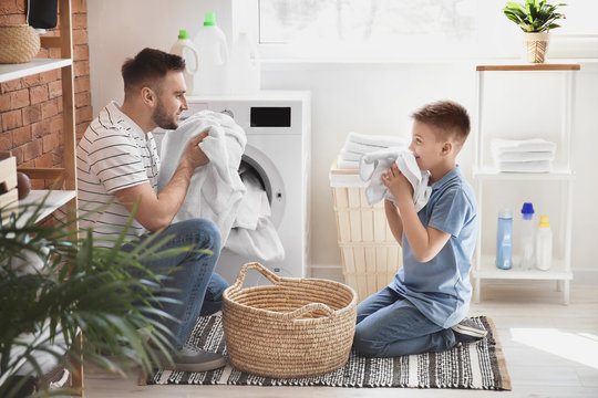 Man and his little son doing laundry at home