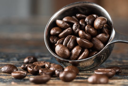 Close-up Of Roasted Coffee Beans In Measuring Cup On Table