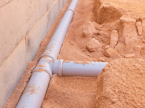 Junction of plastic sewer pipes. Sewage pipeline system of residential building under construction