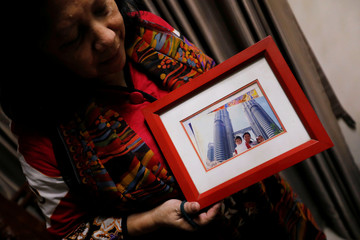 Nina Widyawati, 65-year-old mother of Ratih Purwarini, a doctor who passed away due to the coronavirus disease (COVID-19), shows a photograph of her daughter and grandchildren, at her house in Jakarta