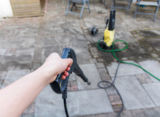 Man using a high pressure syringe to clean tiles. can also be used to remove weeds between tiles.