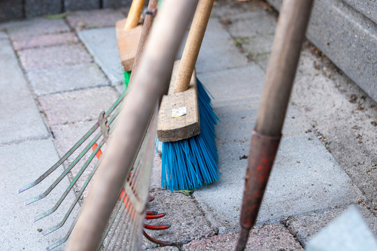 Close up of some Gardening tools. focused on a Broom. tools to clean up a garden.