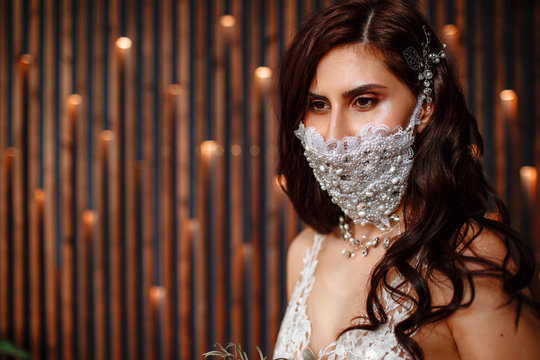 Bride in with a handmade wedding antiviral mask on her face. Wedding bouquet in hand
