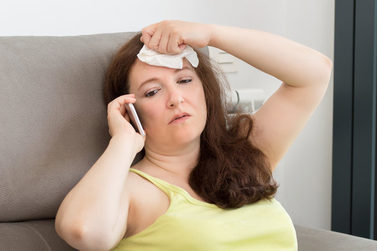 Woman wiping off sweat from forehead and calling the customer service