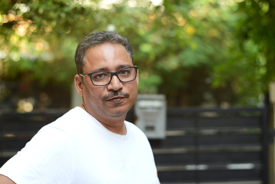 Indian man wearing spectacles in a white t-shirt outside a gate against a gate and a nature background