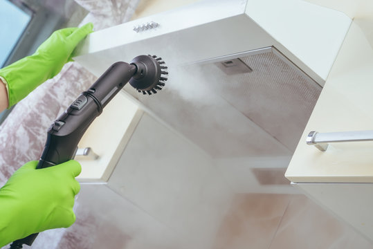 house cleaning. Girl brushes steam cleaners kitchen drawing with steam in green gloves. cleaning of a surface.