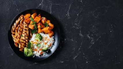 Foto op Canvas Kip close-up of chicken strips, broccoli, rice, yams