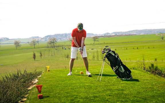 Man in red shirt, white shorts and baseball cap preparing to hit golf ball with club. He has golf clubs next to him. Sports that people around the world play during the quarantine for health.
