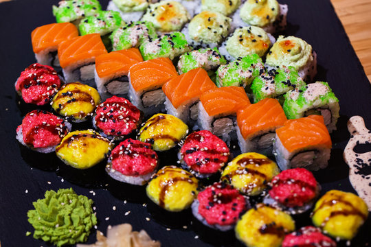 Set of rolls on a black plate with wasabi and ginger