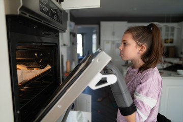 Young girl looking into an oven wearing oven mitts