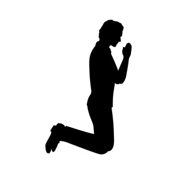 Silhouette of man kneeling praying