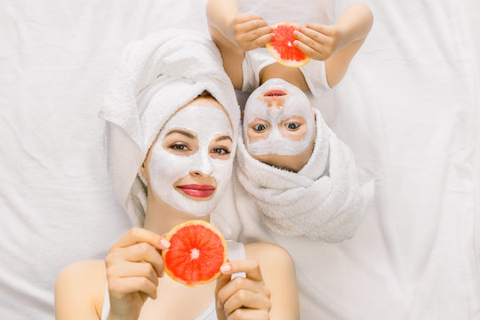 Family beauty treatment in the bathroom. Pretty mother and daughter baby girl make a clay mask for face skin, lying on bed with towels on heads and holding slices of grapefruit in hands