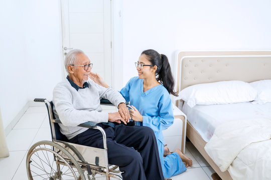 Friendly nurse and old patient smiling together