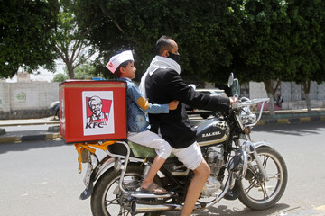 A delivery man wearing a protective face mask rides his motorbike with a boy, amid fear of coronavirus disease (COVID-19), in Sanaa