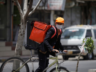 A delivery man wearing a protective face mask rides his bicycle, amid fear of coronavirus disease (COVID-19), in Sanaa