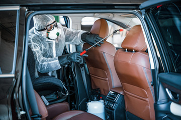Disinfectant worker in protective mask and suit making disinfection of car seats