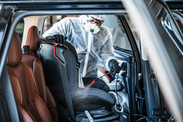 Disinfectant worker in protective mask and suit making disinfection of baby car seat