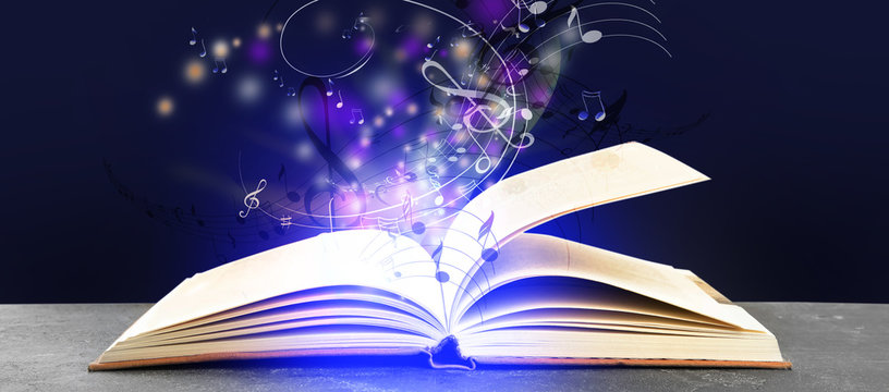 Symphony shining with musical notes from open book on table against dark purple background. Banner design