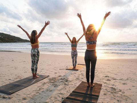 Young caucasian woman practice yoga warrior pose at sunrise seashore