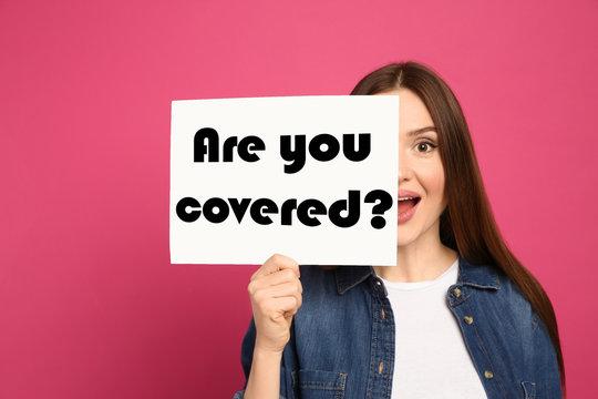 Woman holding paper with text ARE YOU COVERED? on pink background. Insurance concept