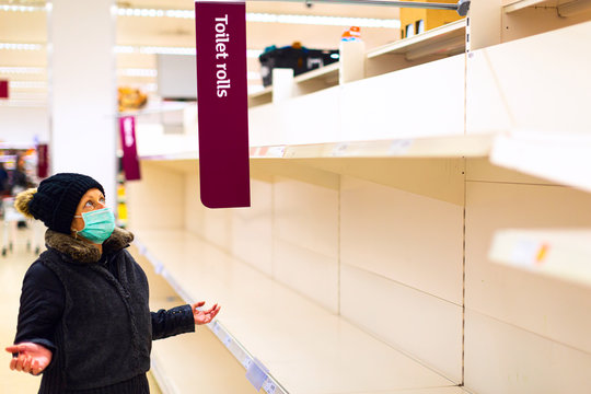 Senior female customer wearing a protective medical mask looks confused at the empty shelves of toilet paper rolls in a supermarket