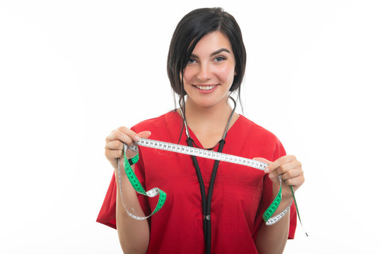 Portrait of young attractive female nurse showing measuring tape