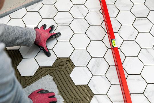 tiler laying marble texture hexagon tiles on the bathroom floor