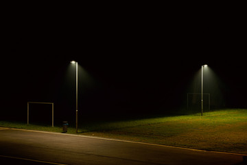 Fotomurales - Illuminated Street Light On Soccer Field At Night By Empty Road