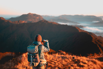 Wall Murals Deep brown Adult female taking photo using her mobile phone at sunrise at Mount Pulag National Park, Benguet, Philippines