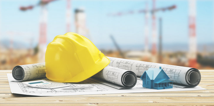 Close-up Of Yellow Hardhat Amidst Blueprints On Table At Construction Site