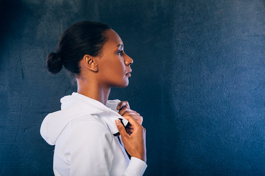 Side view of sporty woman wearing a sport clothes and looking away against black background