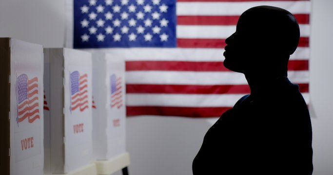MS silhouetted African American man looking at voting booths, with hand over heart, US flag on wall behind