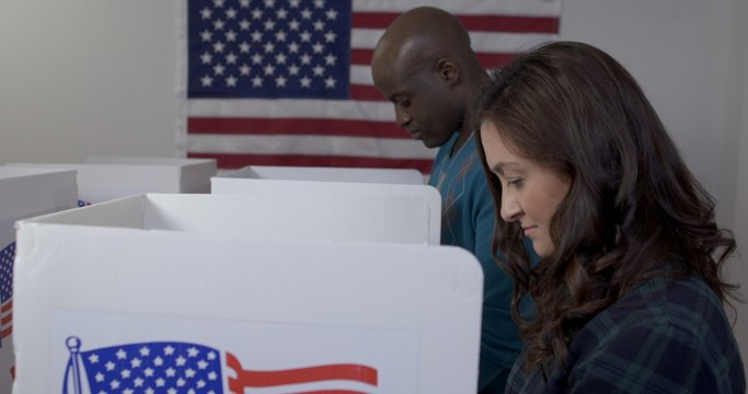 MS side angle view Caucasian woman and African American man casting votes in booths at polling station