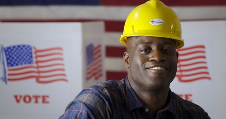 """Close up African American man in plaid shirt wearing hard hat with """"I Voted"""" sticker and turning, smiling in front of polling booths with US flag. Large US flag behind"""