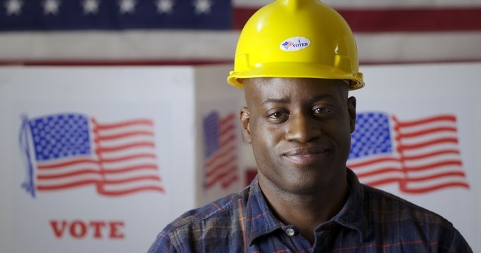 """Close up African American man in plaid shirt wearing hard hat with """"I Voted"""" sticker, facing camera and smiling in front of polling booths with US flag. Large US flag behind"""