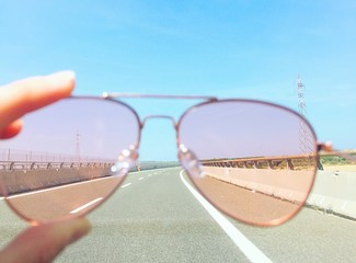 Fotomurales - Cropped Hand Holding Sunglasses Over Road Against Clear Sky