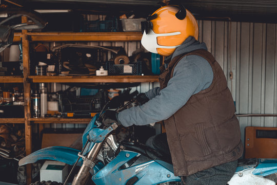 Emoji motocross rider with fancy black nerd sunglasses on his motorcycle inside of garage . Emoji with mask protecting against coronavirus – Covid 19. 3D rendering and photography collage.