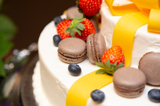 Strawberry cake with brown macaroons and blueberries