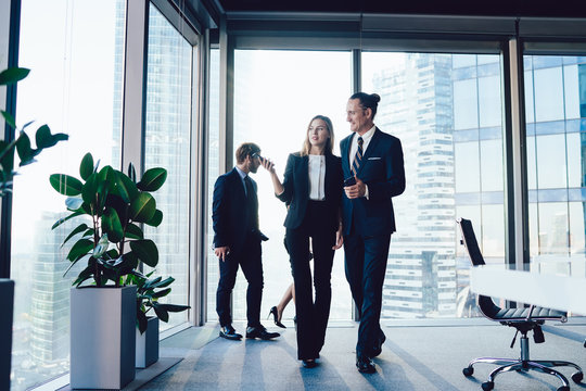 Young confident male and female employees walking in office together having friendly conversation on break, administrative assistant showing male colleague working space discussing cooperation