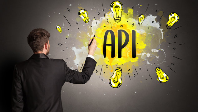 businessman drawing colorful light bulb with API abbreviation, new technology idea concept