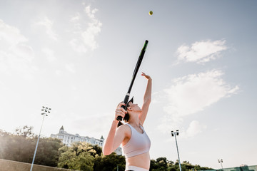 young tennis player tossing ball up on court