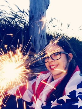 Portrait Of Woman With American Flag Holding Illuminated Sparkler
