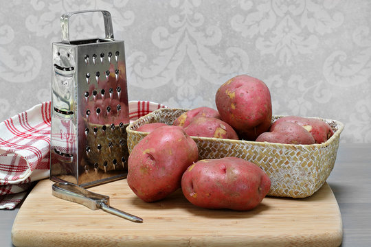 Fresh raw red potatoes in a basket on cutting board with utensils.