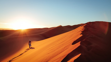 Silhouette Of Woman On Sand Dune In Desert Against Clear Sky