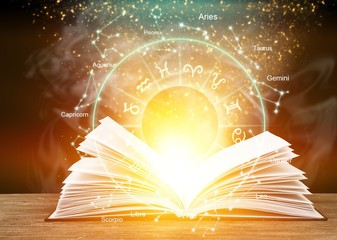 Open book with light astrology illustration on table